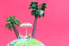 Tragender Badeanzug der Miniaturleute, der auf der Kugel sich entspannt Stockbilder