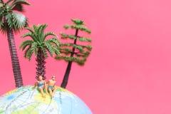 Tragender Badeanzug der Miniaturleute, der auf der Kugel sich entspannt Stockfoto