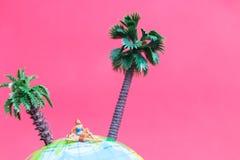 Tragender Badeanzug der Miniaturleute, der auf der Kugel sich entspannt Lizenzfreie Stockbilder