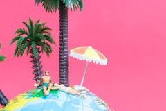 Tragender Badeanzug der Miniaturleute, der auf der Kugel sich entspannt Stockfotos