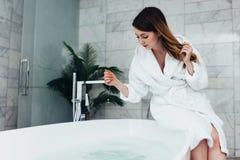 Tragender Bademantel der recht dünnen Frau, der auf dem Rand der Badewanne auffüllend mit Wasser sitzt lizenzfreie stockbilder
