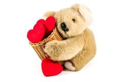 Tragender Bambuskorb des netten Teddybären voll des roten Herzens lizenzfreie stockbilder