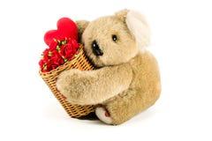 Tragender Bambuskorb des netten Teddybären voll von roten Rosen und von hea lizenzfreie stockfotos
