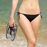 Tragender Bikini der Frau, der Flipflops in ihrer Hand halten geht Lizenzfreies Stockfoto