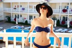 Tragender Bikini der Frau, der im Hotel mit Pool steht stockbilder