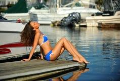 Tragender Bikini und Sonnenbrille der Frau, die auf dem Pier sich entspannen Lizenzfreies Stockfoto
