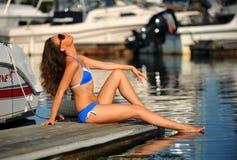 Tragender Bikini und Sonnenbrille der Frau, die auf dem Pier sich entspannen Lizenzfreie Stockbilder