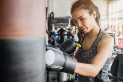 Tragender Boxhandschuh der jungen Frau in der Turnhalle stockfoto