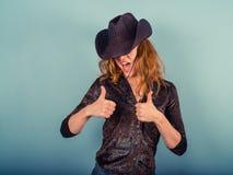 Tragender Cowboyhut der Frau, der Daumen aufgibt Lizenzfreie Stockfotos