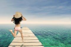 Tragender gestreifter Bikini der Frau, der am Pier läuft Stockfotografie