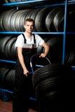 Tragender Gummireifen des jungen Mechanikers im Autoservice Lizenzfreies Stockbild