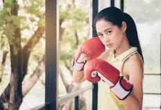 Tragender Handschuhboxer des asiatischen netten Mädchenboxers, setzend mit determ auseinander lizenzfreie stockfotos