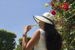 Tragender Hut der Frau und trinkender Champagner im Freien Lizenzfreies Stockbild