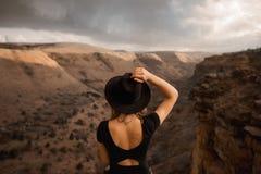 Tragender Hut der jungen Frau, der den canyonand Berg bereitsteht lizenzfreies stockbild