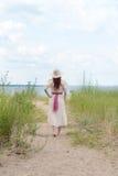 Tragender Hut der Weinlesefrau, der auf Strandweg geht Lizenzfreie Stockfotos