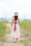 Tragender Hut der Weinlesefrau, der auf Strandweg geht Lizenzfreie Stockbilder