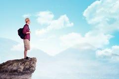 Tragender Hut des asiatischen Reisenden auf die Oberseite des Berges Stockfoto