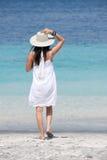 Tragender Hut des Mädchens, der Seebrise genießt Stockbild