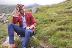 Tragender Hut des Mannes sitzt auf Felsen und schaut weg Lizenzfreies Stockfoto