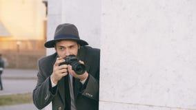Tragender Hut und Mantel des jungen männlichen Spionsmittels, die kriminelle Leute fotografieren und hinter der Wand sich verstec stock video