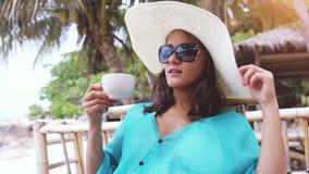 Tragender Hut und Sonnenbrille der jungen eleganten hübschen Frau im Urlaub, sitzend im Strandcafé trinkt Kaffee mit szenischen A stock video