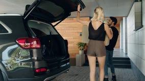 Tragender Kasten der glücklichen Familie vom Auto an der Garage Junge Paare, die auf neues Haus sich bewegen stock footage