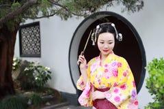 Tragender Kimonogriff traditioneller asiatischer japanischer Frau Geisha ein Fanspiel in einem graden Stockfotos