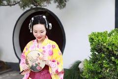 Tragender Kimonogriff traditioneller asiatischer japanischer Frau Geisha ein Fanspiel in einem graden Lizenzfreie Stockbilder