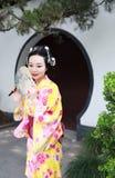 Tragender Kimonogriff traditioneller asiatischer japanischer Frau Geisha ein Fanspiel in einem graden Stockbild