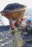 Tragender Kohlenkorb des Mannes auf Kopf Lizenzfreies Stockfoto