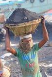 Tragender Kohlenkorb des Mannes auf Kopf Stockbilder
