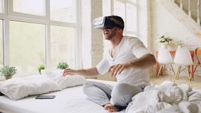 Tragender Kopfhörer der virtuellen Realität des jungen netten Mannes, der Videoerfahrung mit 360 VR beim zu Hause sitzen im Bett  stockbild