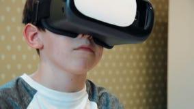 Tragender Kopfhörer der virtuellen Realität des Motorrades des kleinen Jungen Reit stock footage