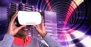 Tragender Kopfhörer der virtuellen Realität der Frau und hohe Gebäude mit Tunnelhintergrund Stockbilder