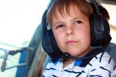 Tragender Kopfhörer des kleinen Jungen im Flugzeug Lizenzfreies Stockfoto
