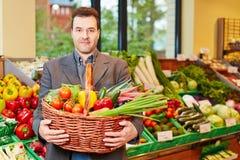 Tragender Korb des Mannes mit Gemüse Stockfotos