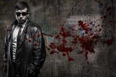 Geheimagentmann auf blutigem Wandhintergrund Stockfoto