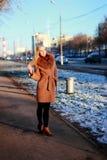 Tragender Mantel der jungen Frau, der hinunter die Straße, im vollen Wachstum geht Stockfotos