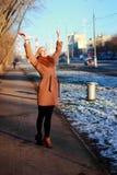 Tragender Mantel der jungen Frau, der hinunter die Straße, kalter Winter DA geht Stockfotos