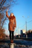 Tragender Mantel der jungen Frau steht auf einem Stand, kalter Wintertag, Han Lizenzfreie Stockfotos