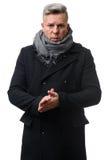 Tragender Mantel des hübschen reifen Mannes stockfoto