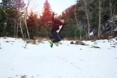 Tragender Mantel und Handschuhe des jungen Kerls, Schnee springend und genießen Stockfotos