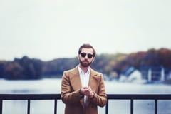 Tragender Mantel und Sonnenbrille des Mannes stockfotos
