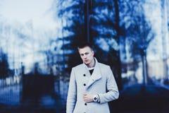 Tragender Mantel und Uhr des Mannes lizenzfreie stockfotografie