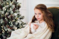 Tragender Pyjama des kleinen Mädchens, der auf dem Lehnsessel eingewickelt in einer Decke mit Feiertagsbettwäsche durch Weihnacht Lizenzfreie Stockfotografie
