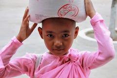 Tragender Reis der jungen Myanmar-Nonne Stockfotos