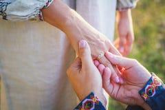 Tragender Ring des Bräutigams auf dem Finger der Braut Lizenzfreie Stockbilder