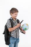 Tragender Rucksack des glücklichen Schülers und Halten der Vergrößerungslinse Lizenzfreie Stockfotos