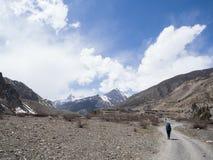 Tragender Rucksack des Reisenden, der zum Dorf und zum Schneeberg in Abstand geht Lizenzfreies Stockbild