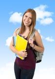 Tragender Rucksack und Bücher des jungen schönen Studentmädchens unter blauem Himmel stockfotografie